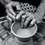 Two hands in black and white form a bowl out of clay on a potters wheel