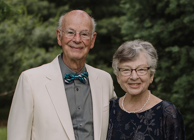 A man in his 70s stands with his arm around his wife who is shorter. He wars a white suit coat and bowtie, she has short hair, glasses, and wears a black dress.